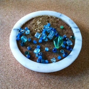 Selected beads on a cork lined marble coaster.
