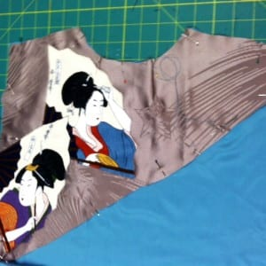 The upper back appliqued section is pinned for basting.