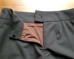 Wool shaped waistband with tab and lining.