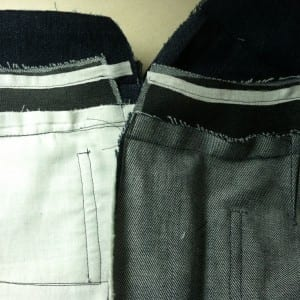 The white tape is fused over the interfacing and then stitched into the seam.