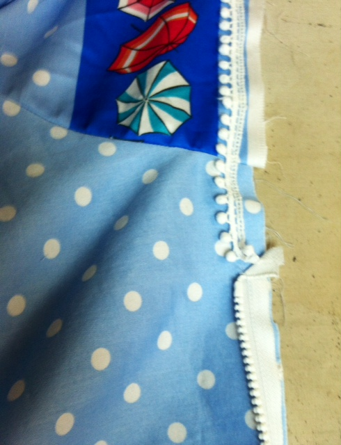 fringe extending above the zipper into the hood.