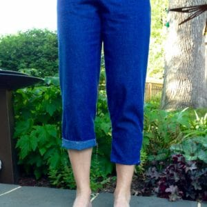 Denim capris with cuffed hem on right leg and more pegging on left leg.
