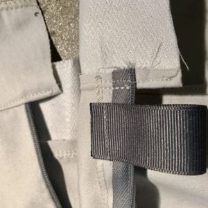 Tab is inserted after facing is attached and understitched, but before turning facing inside.